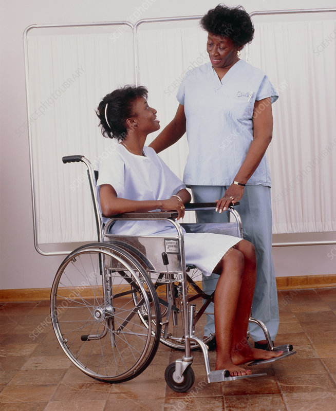 Disabled patient in wheelchair attended by nurse