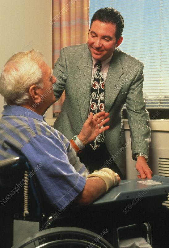 Elderly disabled man in wheelchair with doctor