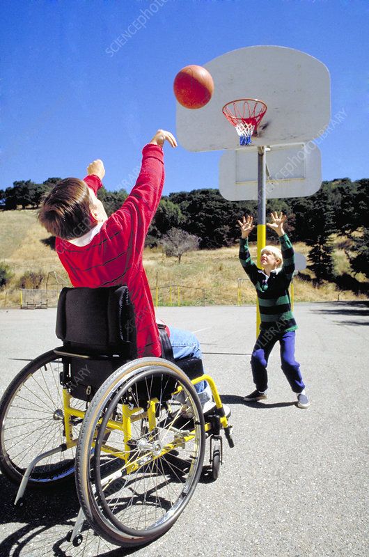 Disabled boy in wheelchair shoots hoops