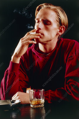 Young man smoking and drinking
