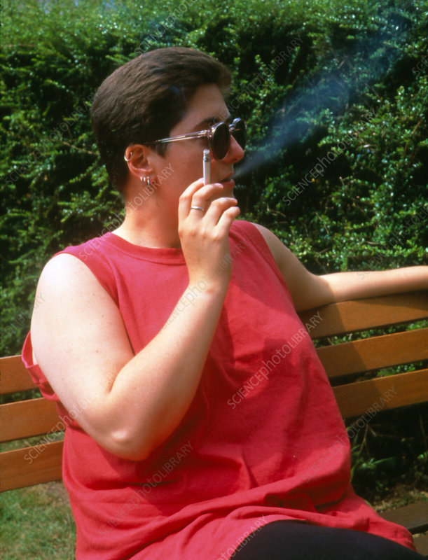 Overweight woman smoking a cigarette.