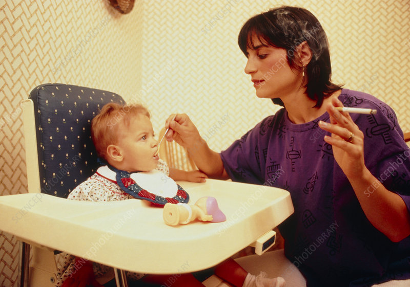 Mother smoking whilst feeding a baby