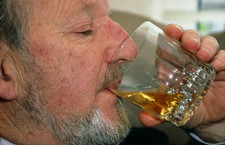 Profile of an elderly man drinking alcohol