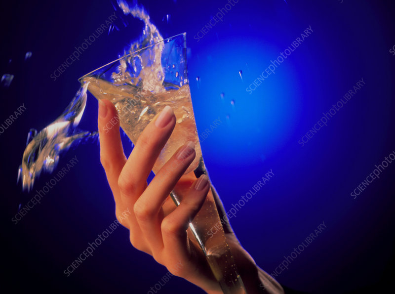 Woman's hand spills glass of alcoholic drink