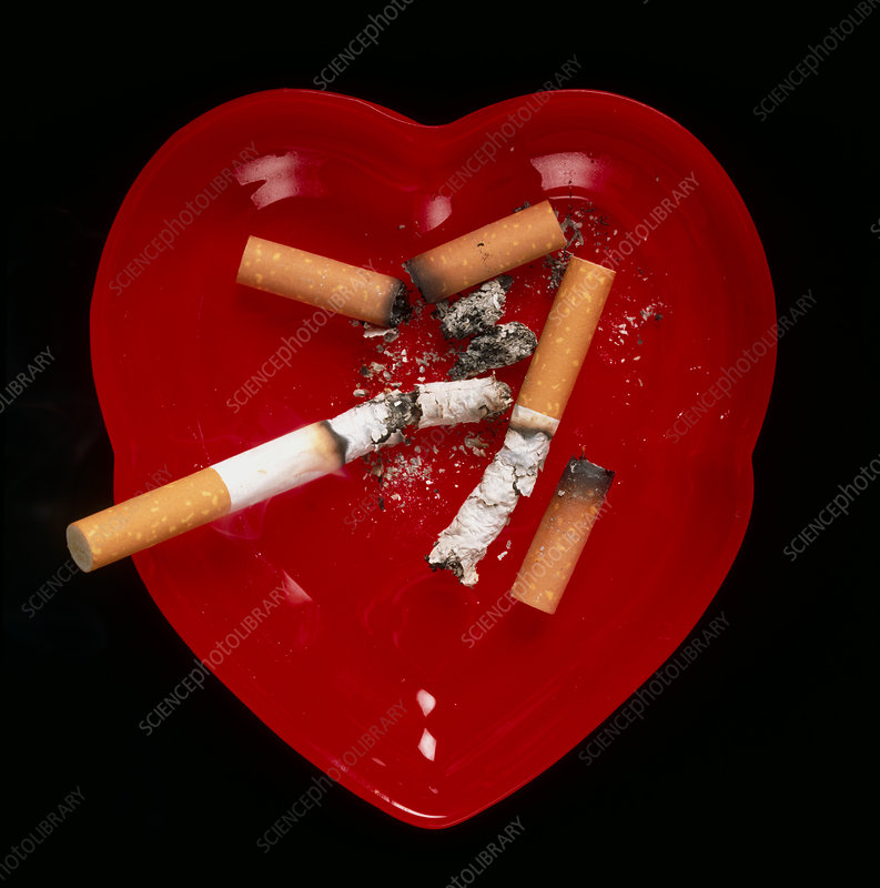 Cigarette butts in red heart-shaped ash tray