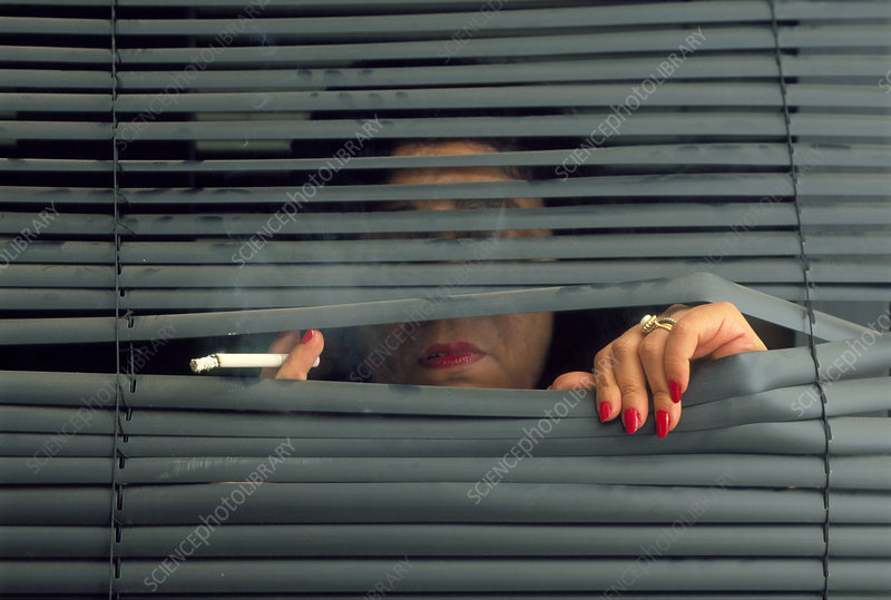 Woman smoking through a blind looking depressed