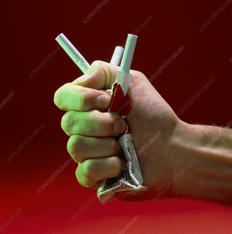 Hand crushing a packet of cigarettes