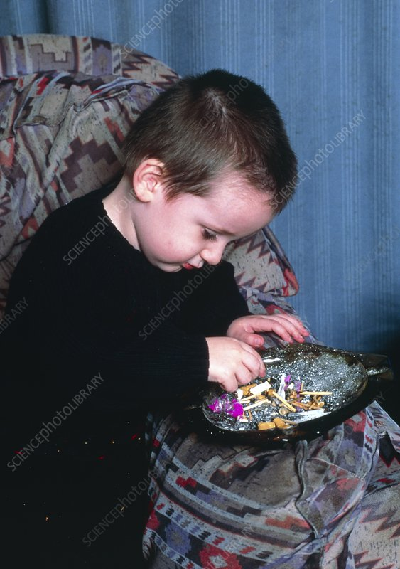 Young boy plays with a full ashtray