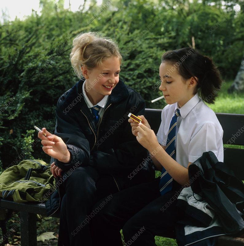 Young teenage girls lighting cigarettes outdoors