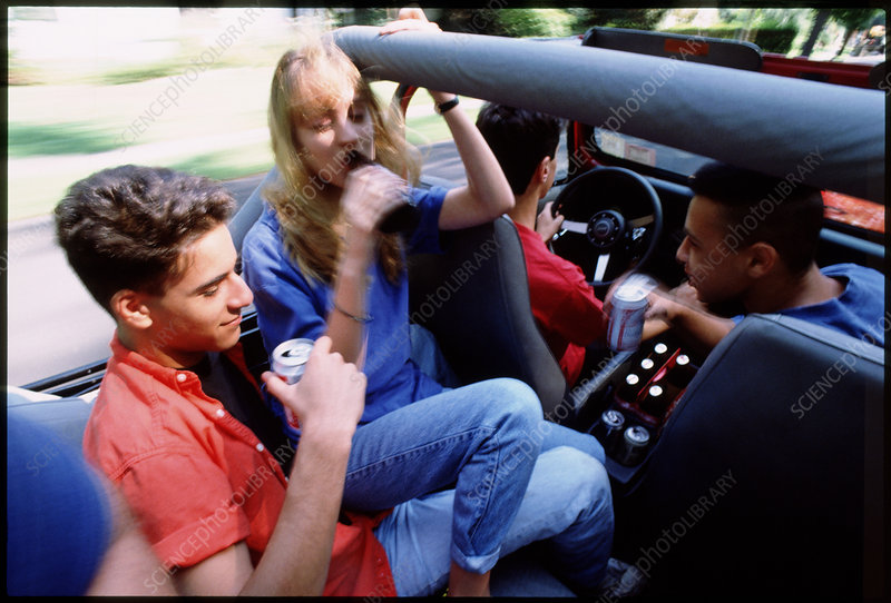 Young teenagers drink beer whilst riding in car