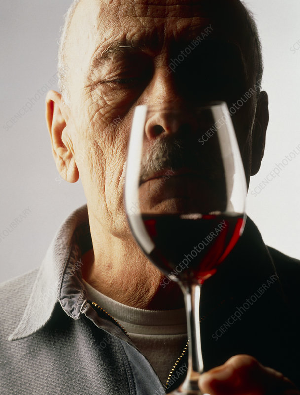 Elderly man examines a glass of red wine