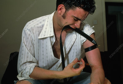 Heroin user about to inject the drug into his arm