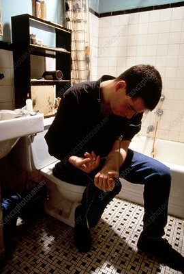 Heroin user injecting arm in bathroom