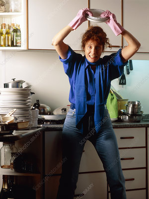 Frustrated woman in kitchen about to smash plates