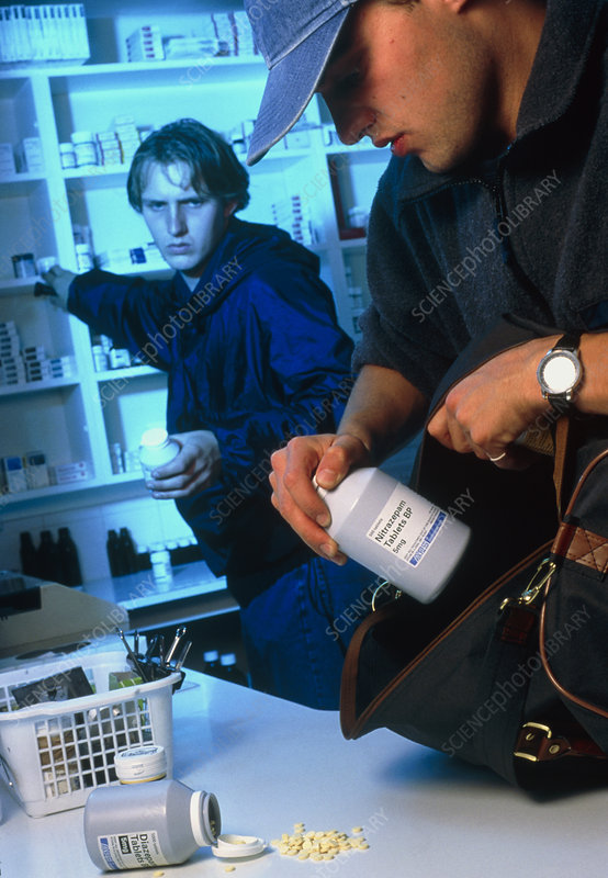Two male youths stealing drugs from a pharmacy