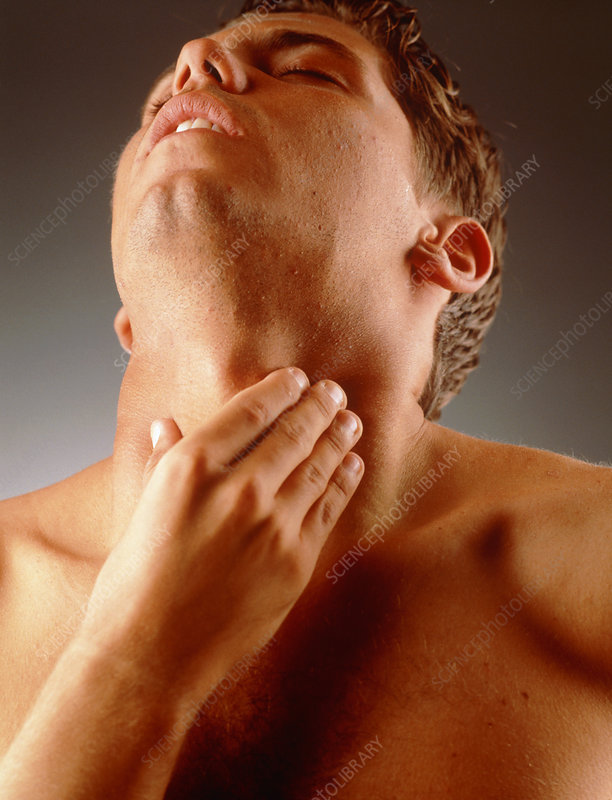 Man holds his neck suffering neck or throat pain