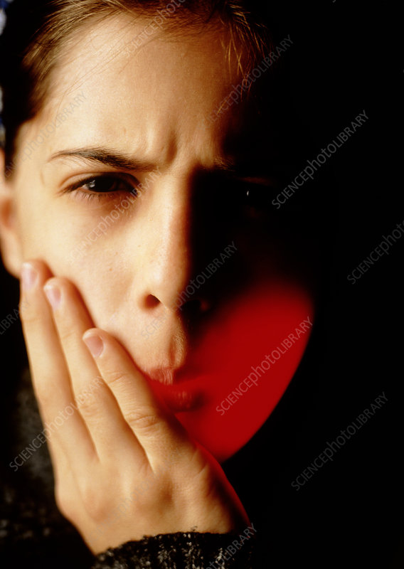 Girl holds the side of her mouth suffering pain