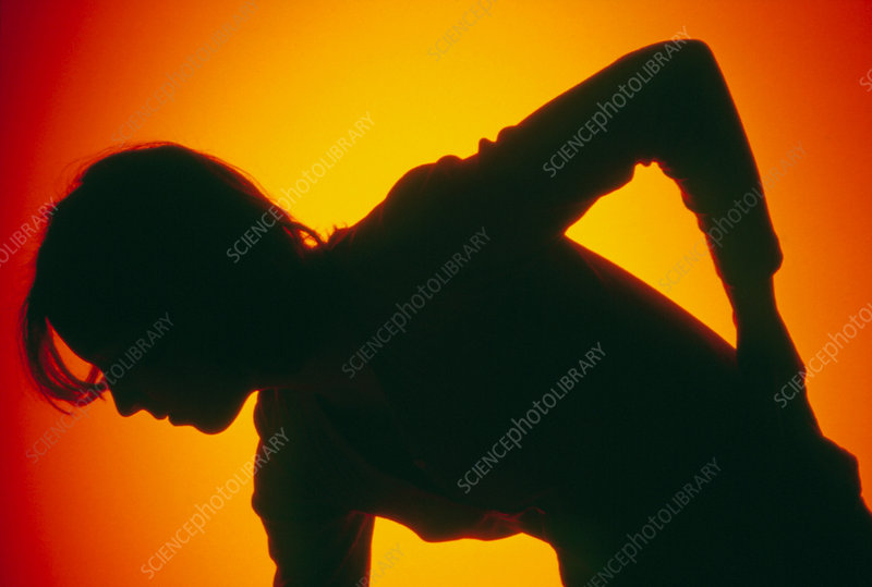 Silhouette of a woman rubbing lower back in pain