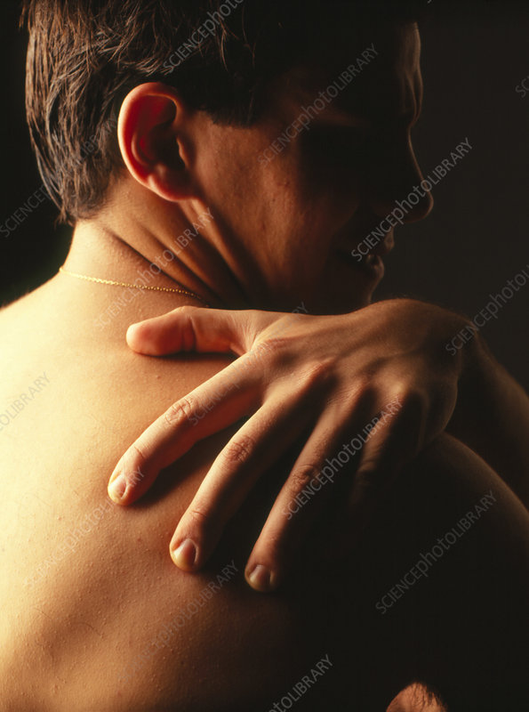 Man holds his shoulder suffering from pain