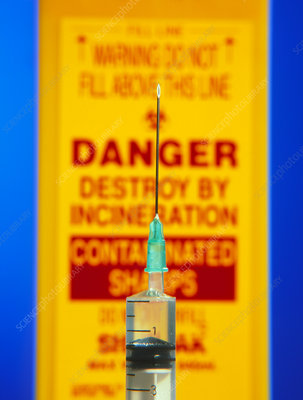 Close-up of syringe in front of sharps bin