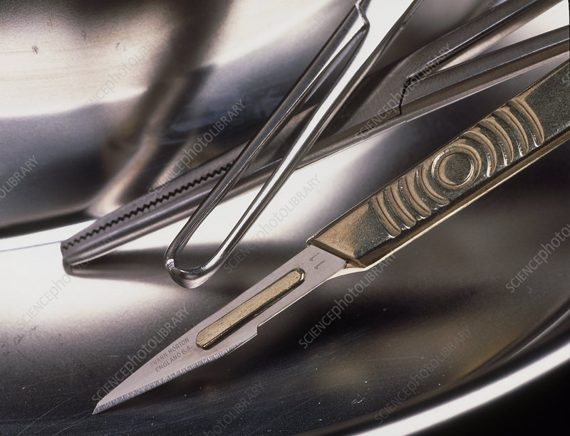Surgical scalpel and forceps in a metal bowl