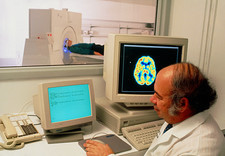 Radiographer performing a PET brain scan