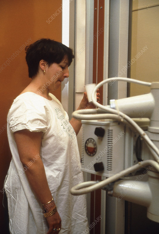 Woman swallowing barium during X-ray examination