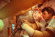 Scientist working through protective glove box