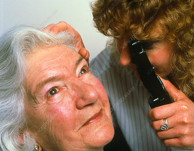 Optician examining the eyes of middle-aged patient