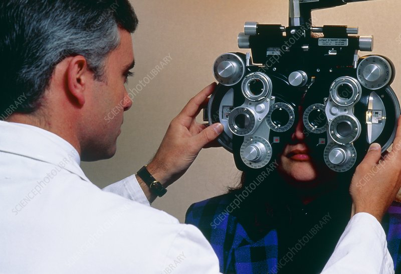 Optician using refracting head to check eyesight