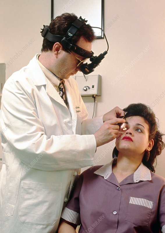 Ophthalmoscope examination of a young woman's eyes