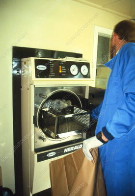 Medical technician operating a hospital autoclave