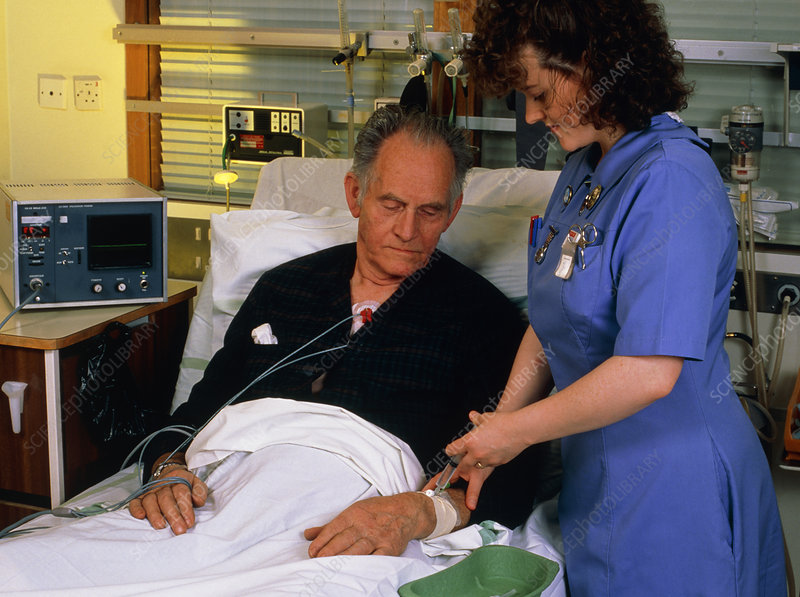 Nurse giving injection to coronary care patient