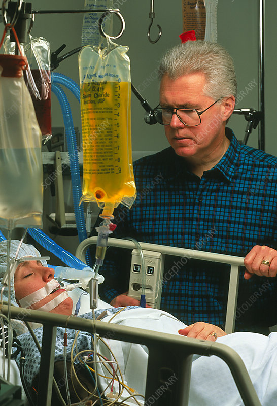 Woman coma patient in intensive care, with visitor