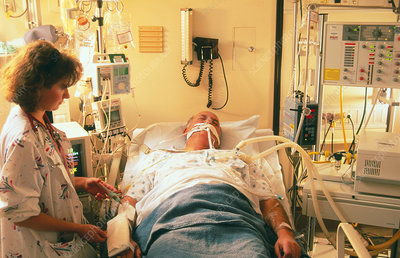 Nurse with cardiac patient in intensive care unit