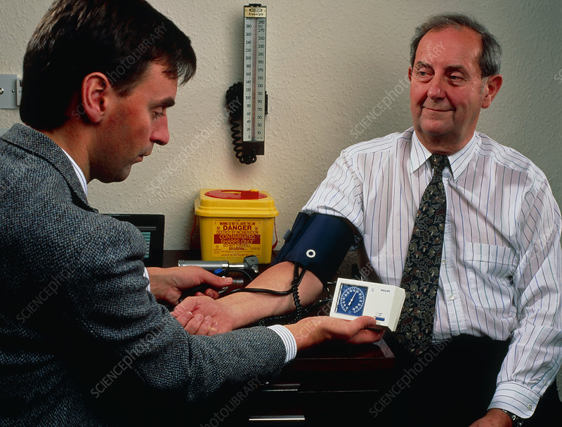 GP measures blood pressure with analogue sphygmo.