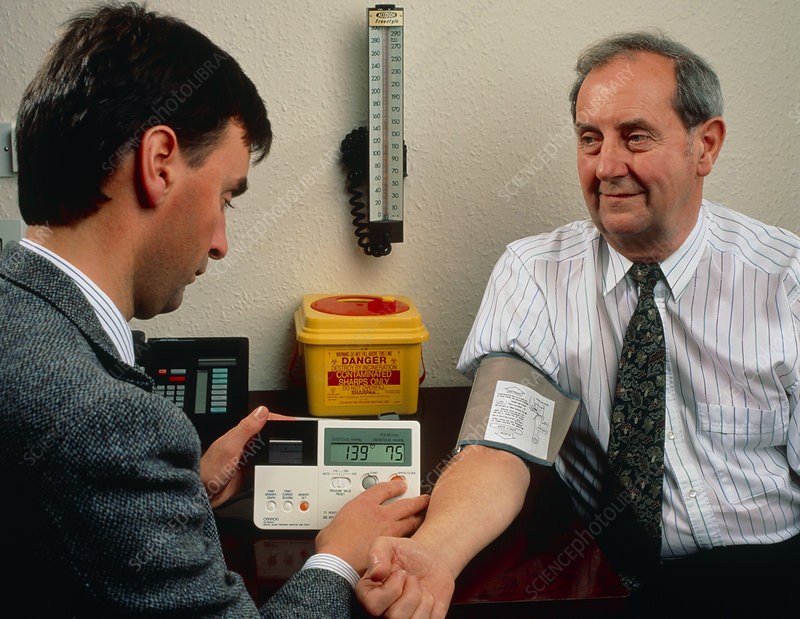 GP measures blood pressure with digital sphygmo.