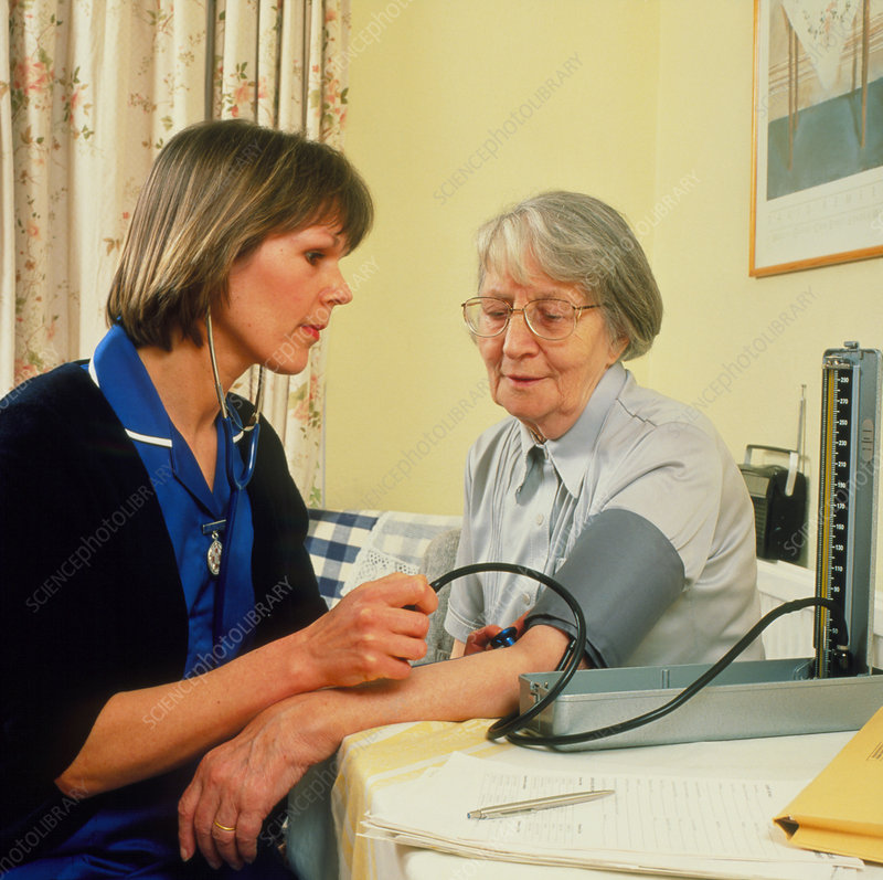 District nurse takes blood pressure of old woman