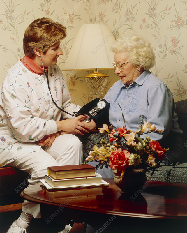 Nurse takes the blood pressure of an elderly woman