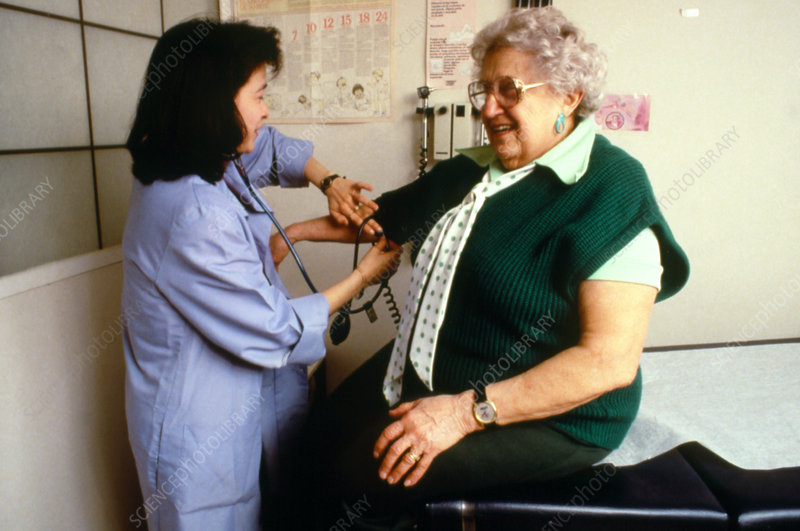 Doctor taking blood pressure of a female patient