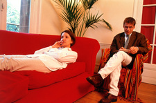Woman lying on a couch undergoing psychoanalysis