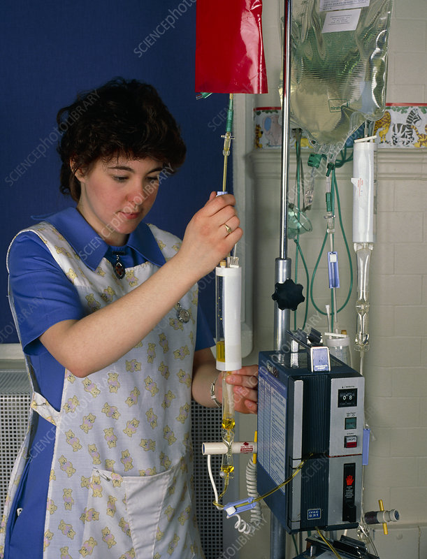Nurse adjusting an infusion pump.