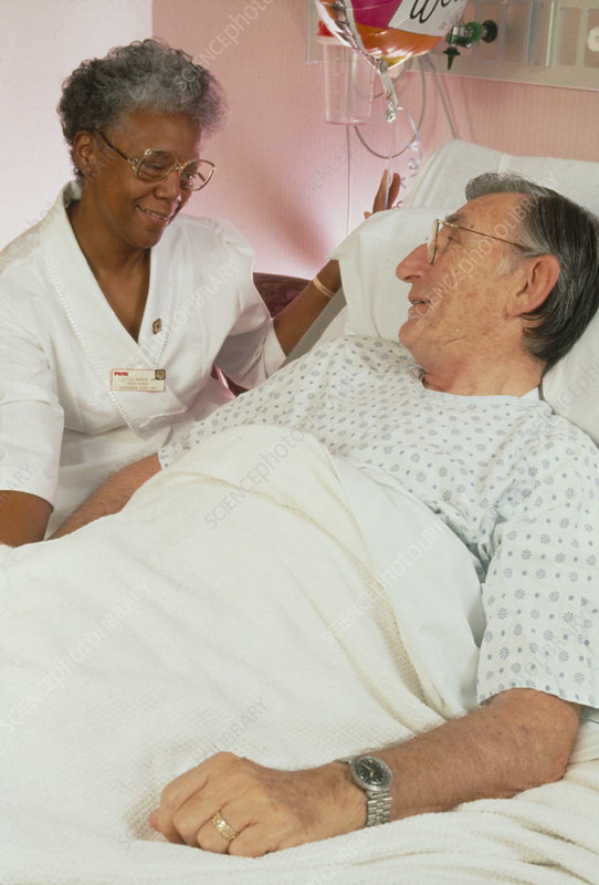 Nurse talking to elderly patient in geriatric ward
