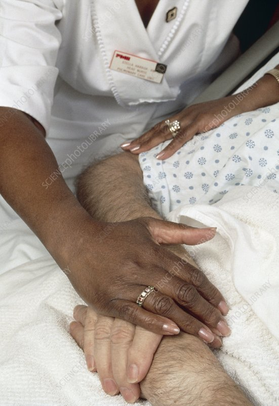 Nurse touching hands of elderly male patient
