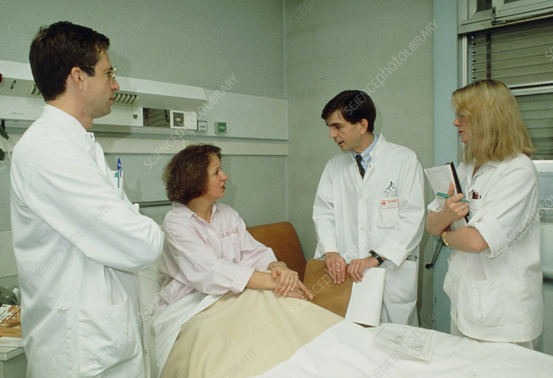 Woman patient with three doctors in hospital ward