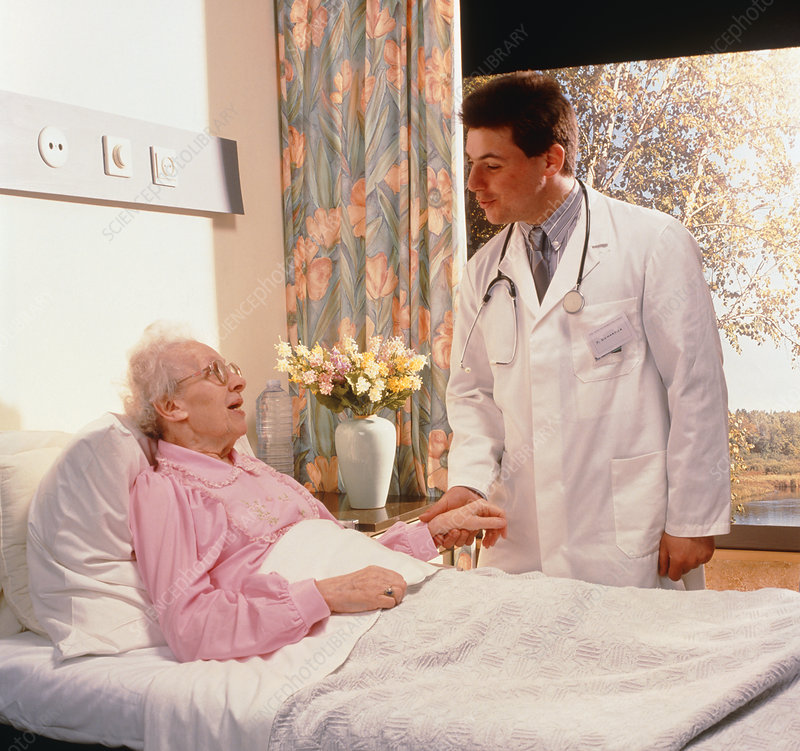 Doctor talking to elderly woman in hospital bed