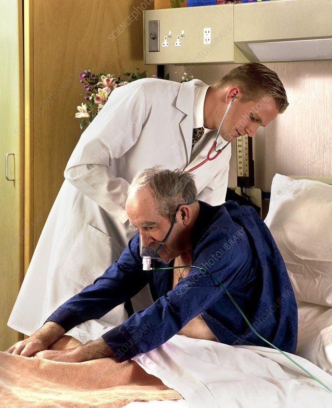 Doctor uses stethoscope on elderly man in ward