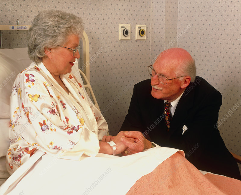 Elderly woman visited by man in a geriatric ward