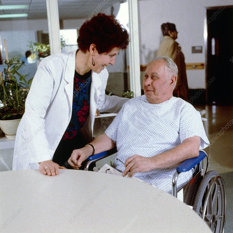 Nurse with an elderly man on a hospital ward