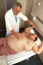 Hospital doctor examines obese man lying on a bed